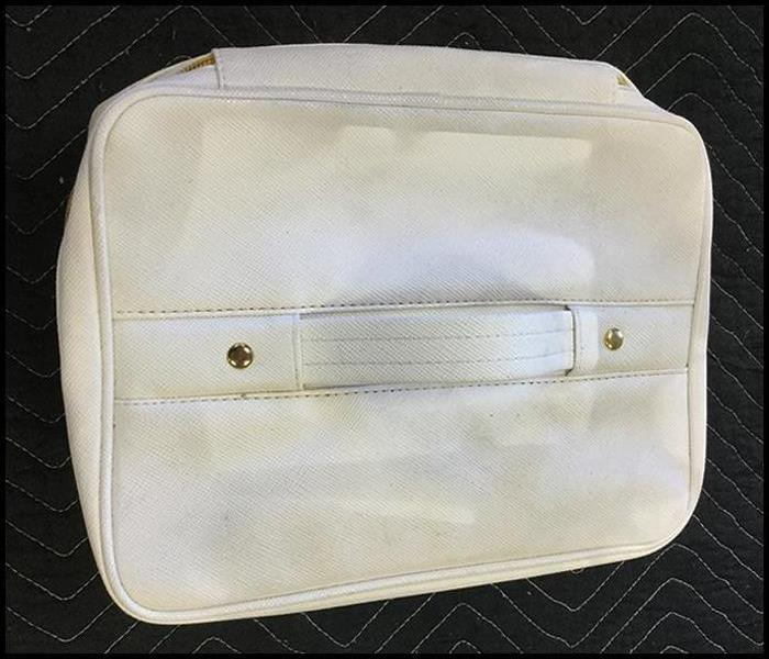 A white canvas bag covered in soot