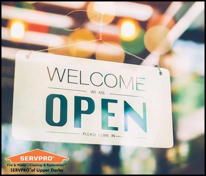 Welcome We Are Open sign hanging on a retail store's door