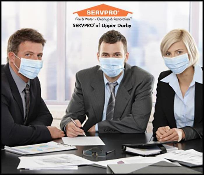 two business men a a business woman sitting at a table wearing a face mask