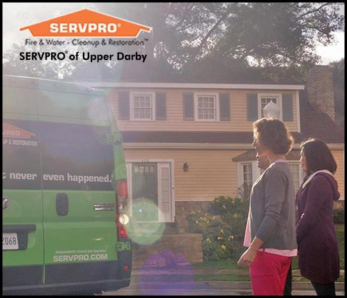 Women standing out front of a home as a SERVPRO van pulls into driveway