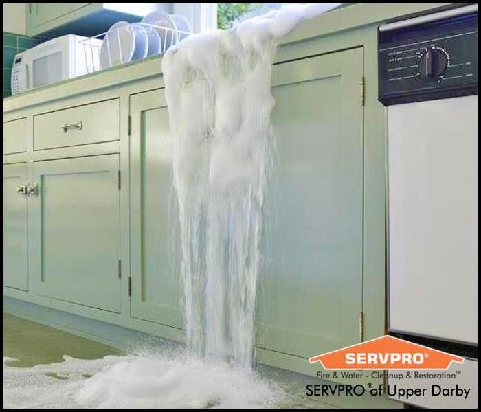 Image of a kitchen sink overflowing and water dripping down green cabinet onto the floor